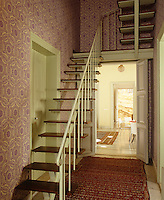 A flight of open slatted wooden stairs with an iron balustrade in a narrow double-height hallway