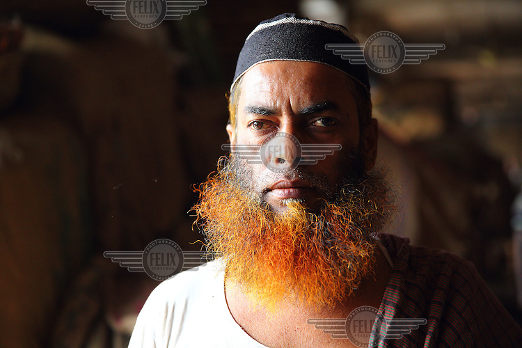 A man with a henna dyed beard.<br /> <br /> It is very common in Bangladesh to see older people with dyed orange hair, men with orange beards or orange moustaches and women with orange hair. The dye used is from the flowering Henna plant. The practice comes from the widely held belief that the Prophet Muhammad dyed his beard and hair. It is also common among people returning from Hajj. Some Muslims believe that henna is the only dye they are free to use for colouring their hair.