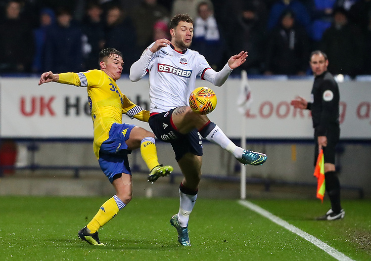 Bolton Wanderers' Yanic Wildschut wins the ball in the air against Leeds United's Jamie Shackleton <br /> <br /> Photographer Andrew Kearns/CameraSport<br /> <br /> The EFL Sky Bet Championship - Bolton Wanderers v Leeds United - Saturday 15th December 2018 - University of Bolton Stadium - Bolton<br /> <br /> World Copyright © 2018 CameraSport. All rights reserved. 43 Linden Ave. Countesthorpe. Leicester. England. LE8 5PG - Tel: +44 (0) 116 277 4147 - admin@camerasport.com - www.camerasport.com
