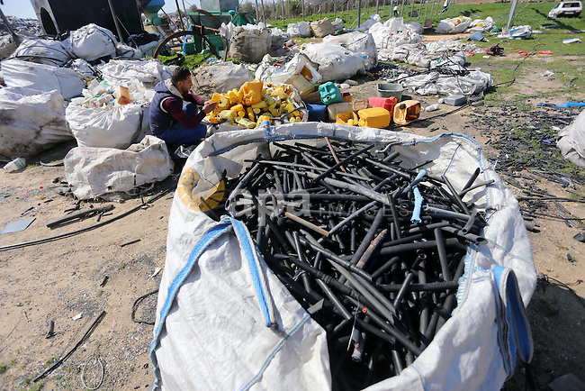 A Palestinian man collects plastics and metals from a pile of waste in Gaza city, February 22, 2017. Workers collect the household recyclables, metals and plastic from landfill and garbage to sell to the local factories. Photo by Mohammed Asad
