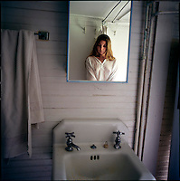 Woman's reflection in bathroom cabinet mirror