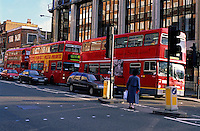 Woman waiting for three double decker buses to pass by before crossing a city street, London, England, UK.