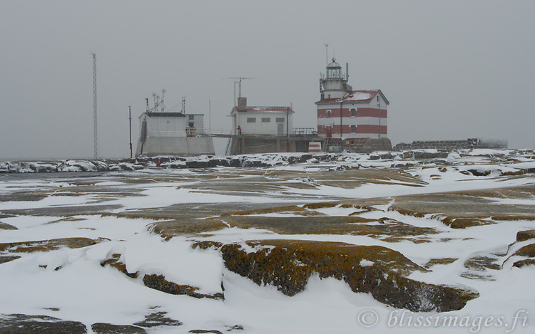 Mossy rocks show muted colours in a light snowfall at Märket lighthouse - Sea of Åland, Finland