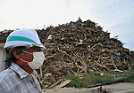 September 8, 2011, Minami-Sanrikucho, Japan - A masked worker stands in front of a heap of debris and rubbles that needs to be removed as recovery and reconstruction progress in Minami-Sanrikucho, Miyagi Prefecture, some 395km northeast of Tokyo, on Thursday, September 8, 2011. September 11 marks the six months since the devastating earthquake shook much of the northeastern region and swallowed up whatever the quake missed in its wake. The death toll reaches over 15,000 with more than 4,500 people still missing. according to the National Police Agency. (Photo by Natsuki Sakai/AFLO) [3615] -mis-