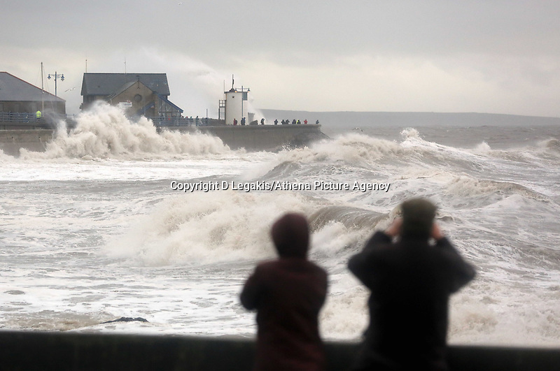 WEATHER PICTURE WALES<br /> Pictured: Wavewatchers watch the giant waves as they crash against the lighthouse wall in the seaside town of Porthcawl, south Wales, UK. Wednesday 05 February 2014<br /> Re: Strong winds combined with high tides cause flood warnings in many parts of the UK