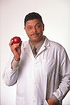 portrait of doctor in lab coat holding apple