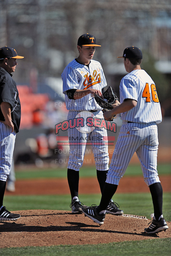 Tennessee Volunteers starting pitcher Kyle Serrano #11 hands over the ball to reliever Andy Cox #46 during a game against the UNLV Runnin' Rebels at Lindsey Nelson Stadium on February 22, 2014 in Knoxville, Tennessee. The Volunteers defeated the Rebels 5-4. (Tony Farlow/Four Seam Images)