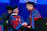 The Rev. Dennis H. Holtschneider, C.M., right, president of DePaul University, congratulates Rick Kash, vice chairman of the global consumer information analytics firm Nielsen, after he was hooded by Ray Whittington, dean of the Driehaus College of Business,   Sunday, June 11, 2017, during the DePaul University Driehaus College of Business commencement ceremony at the Allstate Arena in Rosemont, IL. (DePaul University/Jamie Moncrief)
