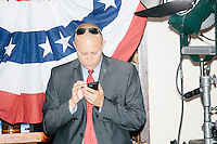 A campaign worker looks at his phones as Republican presidential candidate and governor of Wisconsin Scott Walker speaks at a meet and greet with veterans at the Derry VFW in Derry, New Hampshire.