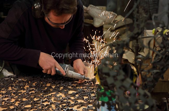 Nicolas Desbons, metalworker and artist, cutting steel for a sculpture made from cross-sections of steel tubes manipulated into organic profiles and soldered together, in his Soleil Rouge workshop, photographed in 2017, in Montreuil, a suburb of Paris, France. Desbons works mainly in steel but often in conjunction with other materials such as fibreglass, glass and clay, using both cold metal and forge techniques. He produces both figurative and abstract sculptures as well as furniture and lighting. Picture by Manuel Cohen