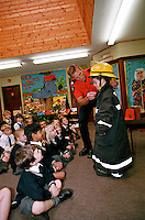 Firefighters on a visit to a local primary school. Children are being taught on what to do in case of fire at home. They are given a talk and shown a video. Cornwall County UK. This image may only be used to portray the subject in a positive manner..©shoutpictures.com..john@shoutpictures.com