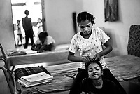 Sarsauti Madkam (11) helps Samukta Sunnam (11) doing her hair at Sukma Football academy girls' hostel. Sukma, Chattisgarh, India. Arindam Mukherjee