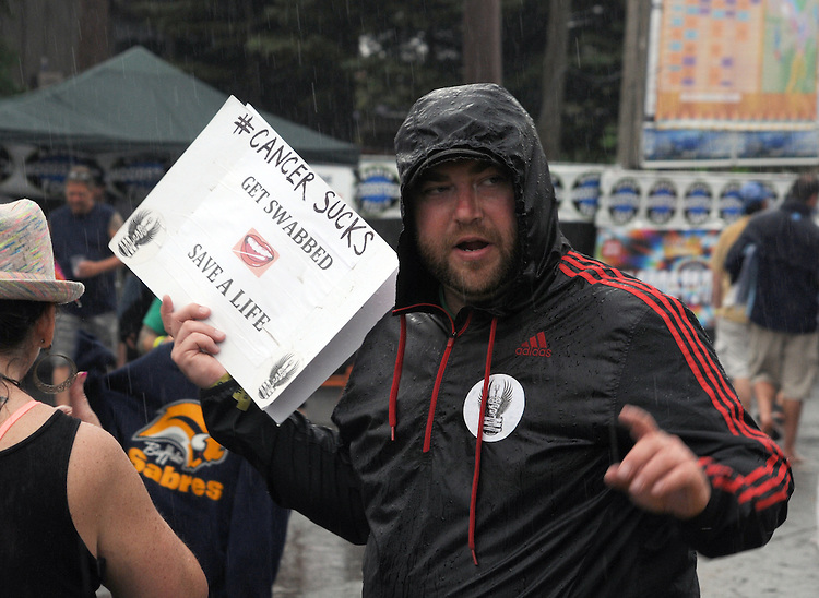 A man urging people to register their bone marrow for possible use in transplants, seen at work in the rain at Mountain Jam Music Festival of 2015, in Hunter, NY on Friday June 5, 2015. Photo by Jim Peppler. Copyright Jim Peppler 2015.