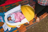 SERBIEN, 08.2016, Kelebija. Internationale Fluechtlingskrise: An der mit Zaeunen abgesperrten ungarischen Grenze stauen sich Fluechtlinge und Migranten. Sie bitten meist vergebens um Einlass in die  Asyl- und Transitzonen (blaue Container). So haben sich auf serbischer Seite provisorische Lager mit sehr schlechten Bedingungen gebildet. | International refugee crisis: Refugees and migrants have been piling up at the fenced-off Hungarian border. They are waiting for entrance into the asylum and transit zones (blue containers), mostly in vain. Thus provisional camps have emerged on the Serbian side with very bad conditions. In the picture mother Noor Mahmud.<br /> © Szilard Vörös/EST&OST