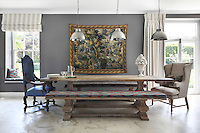 An antique refectory table with benches and industrial-style pendant lights from Maisons du Monde, compliment a tapestry on the grey wall of the dining area