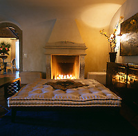 One of the entertaining areas is furnished with a double daybed infront of a stone fireplace filled with candles