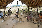 Lepolosi, Kenya. Gold prospectors in a thatched shelter crushing rock with a hammer, sieving it into a pan.