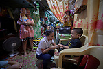 Ella Manio, a student in the Mary Johnston College of Nursing in Manila, helps 5-year old Akim Balaza cut his fingernails during a visit to the boy's home in the Parola neighborhood of Manila's Tondo section. His mother Nelda looks on while holding her 1-year old son Ibo.<br /> <br /> Manio and other nursing students regularly visit the neighborhood to do health education and monitor the health of residents. The students also run a feeding program for neighborhood children.<br /> <br /> The nursing school is supported by United Methodist Women.