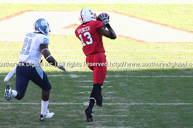 November 28, 2009: North Carolina State wide receiver Owen Spencer #13 takes a touchdown pass into the endzone as North Carolina safety Da'Norris Searcy #21 pursues. The North Carolina State Wolfpack defeated the University of North Carolina Tarheels 28-27 at Carter-Finley Stadium in Raleigh, North Carolina.