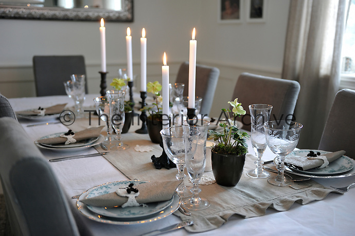 A table laid with silver cutlery, antique plates, a crisp tablecloth and crocheted napkins, is ready for Christmas dinner