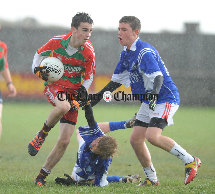 Paul Culligan of West Clare Colleges in action against Darragh Duggan and James Tierney of St. Flannan's during the Munster Colleges U-15a championship at Miltown Malbay. Photograph by John Kelly.
