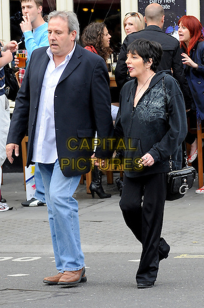 LIZA MINNELLI & FRIEND.Seen walking through the theatre district in London's West End, England, UK, June 1st 2011..full length black tracksuit sweat pants hoodie  bag trousers holding hands  jeans blazer  white shirt .CAP/IA.©Ian Allis/Capital Pictures.