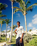 BERMUDA, Cambridge Resort, portrait of waiter gesturing in front of palm trees