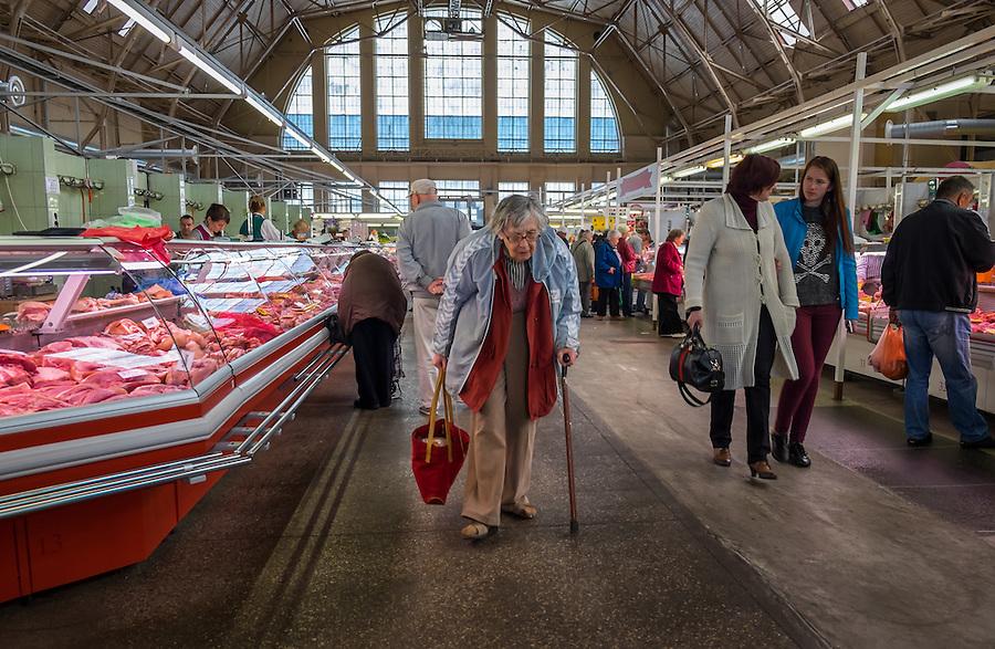 RIGA, LATVIA - CIRCA MAY 2014: Old woman walking in Riga Central Market