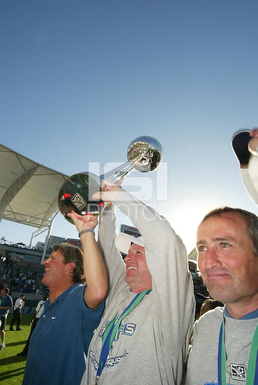 San Jose Earthquakes head coach Frank Yallop, center, carries the MLS Cup with assistant coach Dominic Kinnear, right, and goalkeeper coach Tim Hanley, left,after defeating the Chicago Fire 4-2 in the MLS Championship, in Carson, Calif.