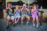 Four brothers and sisters enjoy snow cones while sitting on the bench in front of Schneider's Bakery on State Street in Uptown Westerville during July's Fourth Friday celebration.