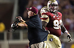 FSU defensive tackle Anthony McCloud pulls defensive coordinator Mark Stoops off the field as he tries to direct his defense against the 9th ranked Clemson Tigers in their NCAA football game at Doak Campbell Stadium in Tallahassee, Florida September 22, 2012.