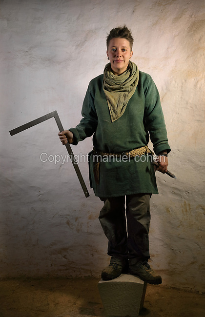Aline Meunier, stone cutter on the Guedelon project since 01/08/2014, wearing medieval costume, holding a set square and chisel, and standing on a keystone, at the Chateau de Guedelon, a castle built since 1997 using only medieval materials and processes, in Treigny, Yonne, Burgundy, France. The Guedelon project was begun in 1997 by Michel Guyot, owner of the nearby Chateau de Saint-Fargeau, with architect Jacques Moulin. It is an educational and scientific project with the aim of understanding medieval building techniques and the chateau should be completed in the 2020s. Picture by Manuel Cohen