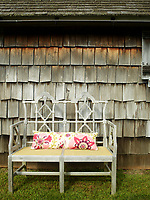 A wooden bench is set outside the cottage with a pretty pink and yellow floral cushion.