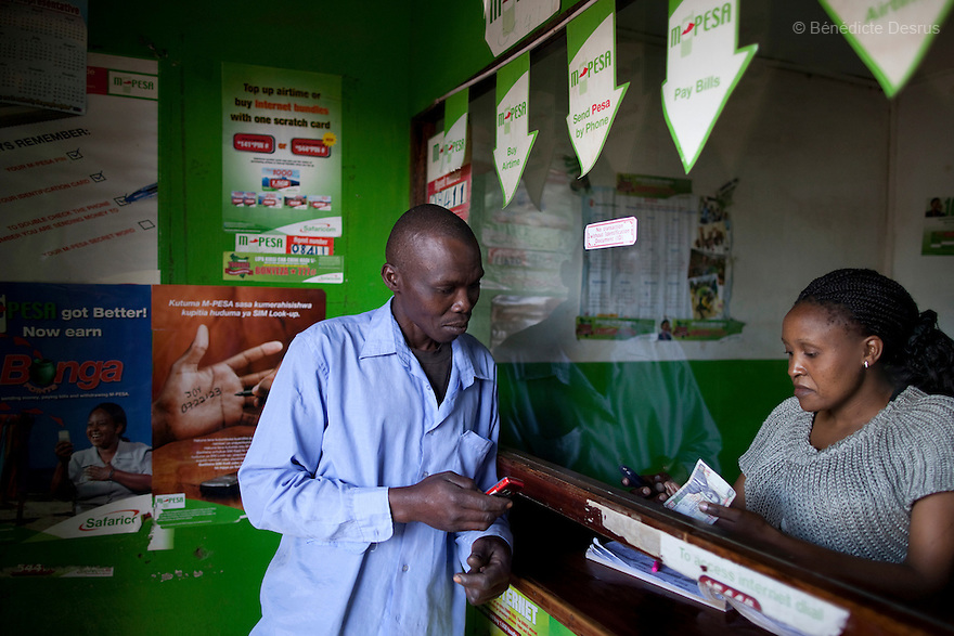 16 december 2012 - Nairobi, Kenya - Customers at an M-Pesa service outlet in Gatina slum, Nairobi. M-Pesa is a mobile-phone based money transfer and microfinancing service for Safaricom and vodacom, the largest mobile network operator in Kenya and Tanzania. Currently the most developed mobile payment system in the developing world, M-Pesa allows users with a national ID card or passport to deposit, withdraw, and transfer money easily with a mobile device. Photo credit: Benedicte Desrus