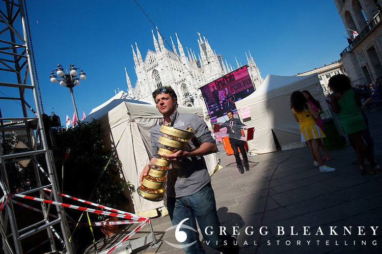 The corkscrew shaped Giro trophy (soon to be hoisted high by Alberto Contador) being transported to the stage--followed by the trophy case.