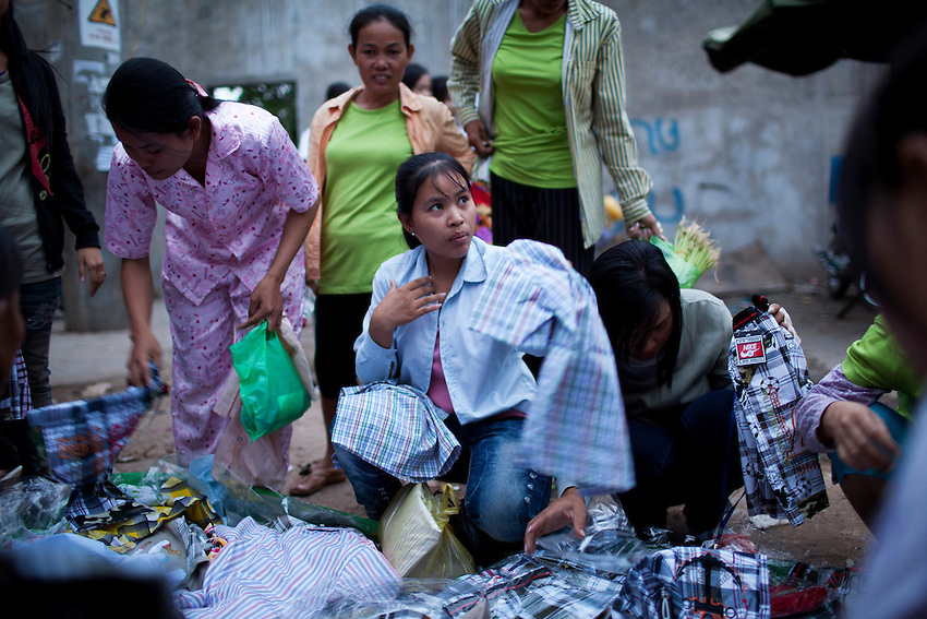 Workers from the Shen Zhou garment factory shop for clothes at a small open-air market just outside the factory in Phnom Penh, Cambodia, September 8, 2011. Clothes like pajamas, which are often worn outside the home in Cambodia, cost around US$2 to $2.50 per set.