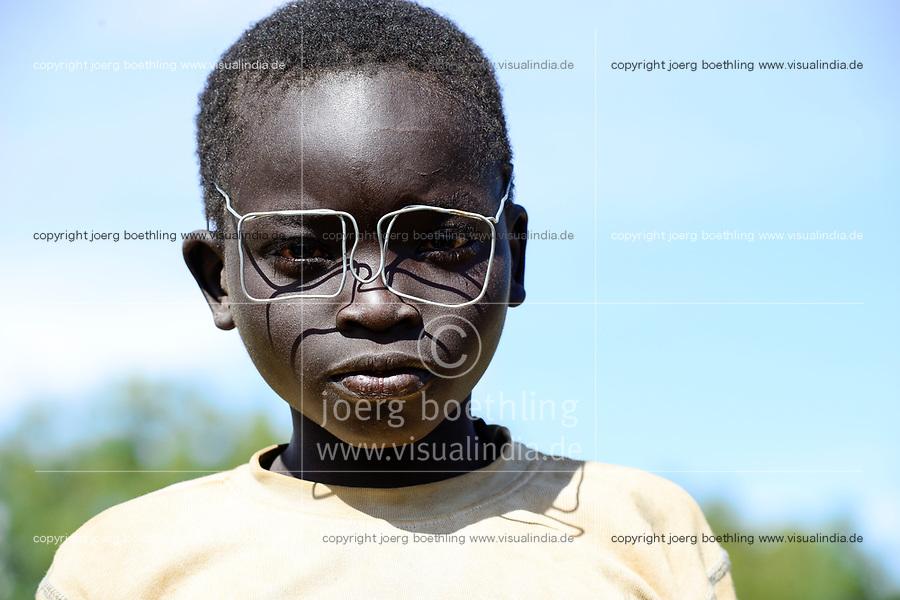 UGANDA, Karamoja, Kaabong,  village Lochom, Karamojong tribe, boy with wire specs, /Junge mit Drahtbrille