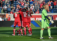The Chicago Fire celebrate a goal by Patrick Nyarko as dejected New England goalkeeper Matt Reis (1) walks back to the net.  Nyarko blocked an attempted clearance by Reis to score an empty net goal.  The Chicago Fire defeated the New England Revolution 3-2 at Toyota Park in Bridgeview, IL on Sept. 25, 2011.