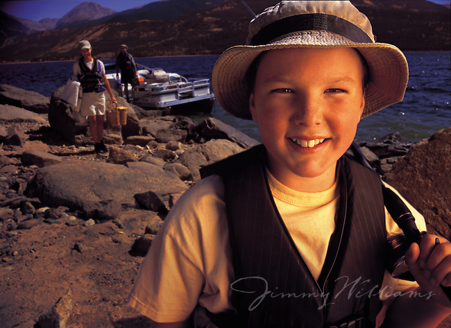 A young boy smiles while out fishing with his family at a lake in Colorado
