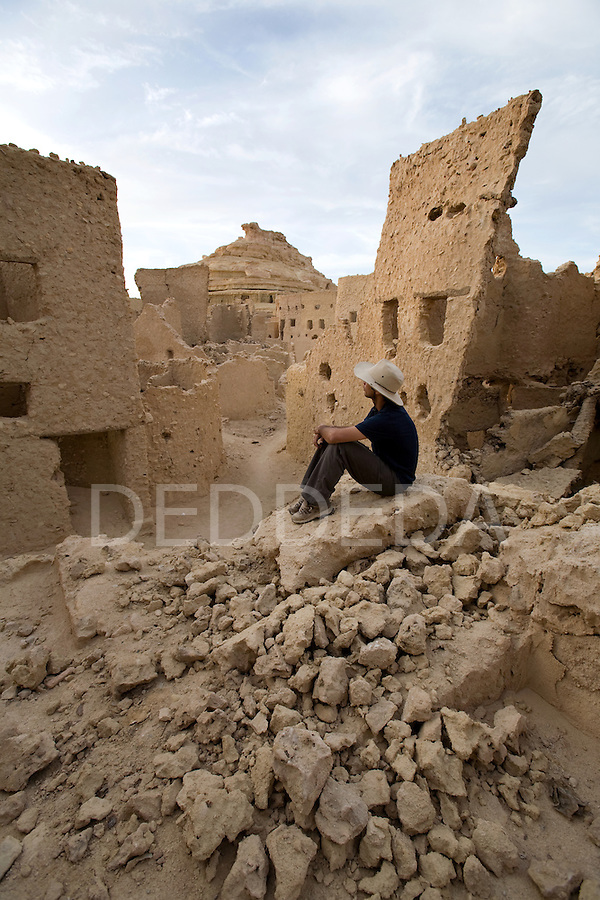 A man in his early 30's, sits inside the 13th century mud-brick fortress of Shali, at sunset, in Siwa Town of the Siwa Oasis, near the Libyan border in Egypt.
