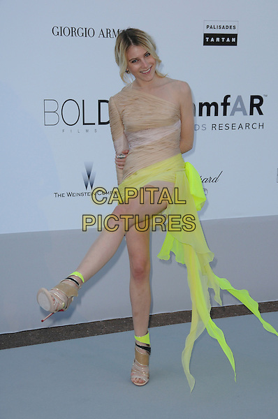 DREE HEMINGWAY.arrivals at amfAR's Cinema Against AIDS 2010 benefit gala at the Hotel du Cap, Antibes, Cannes, France during the Cannes Film Festival.20th May 2010.amfAR full length beige neon yellow dress ruched silk mini sandals one shoulder nude sleeve open toe shoes boots ankle kicking leg .CAP/CAS.©Bob Cass/Capital Pictures.