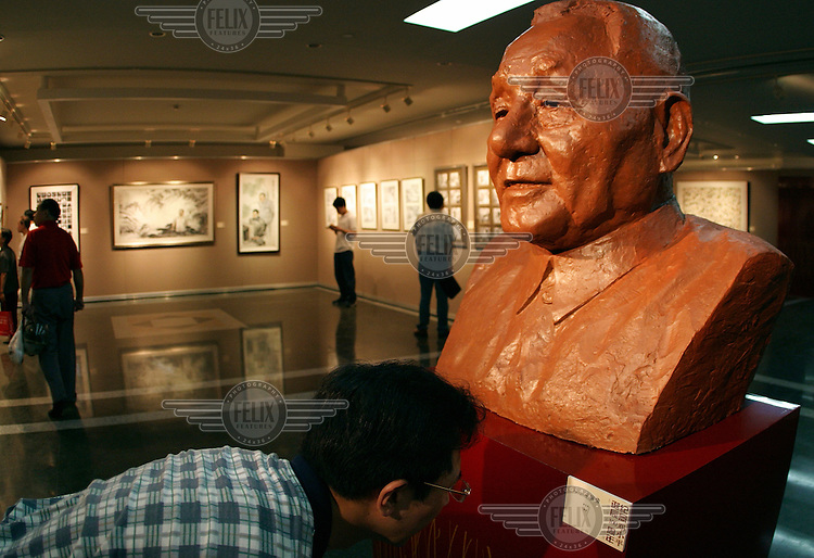 A visitor takes a close look at the inscription below a large bust of the late Chinese leader Deng Xiaoping at an art and photography exhibition commemorating the 100th anniversary of his birth.