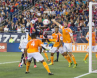 New England Revolution midfielder Diego Fagundez (14) leaps to head a corner kick as Houston players defend.  The New England Revolution played to a 1-1 draw against the Houston Dynamo during a Major League Soccer (MLS) match at Gillette Stadium in Foxborough, MA on September 28, 2013.
