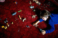 "Rowan, a five-year-old autistic child, playing with plastic animal toys in a hotel room during an expedition across Mongolia. Rowan, who has been nicknamed ""The Horse Boy"", embarked on a therapeutic journey of discovery with his parents to visit a succession of shaman healers in one of the most remote regions in the world. Following Rowan's positive response to a neighbour's horse, Betsy, and some reaction to treatment by healers, Rowan's parents hoped that the Mongolian shamanistic rituals along the route and the prolonged contact with horses would help to unlock their son's autism and assist his development.."