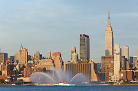"WEEHAWKEN, NJ - JULY 4: FDNY fire boat Marine 1 ""John D. McKean"" puts on a water show on the Hudson river, with the Empire State Building and Manhattan skyline in the background, prior to the annual Macy's Fourth of July fireworks on Saturday, July 4, 2009."