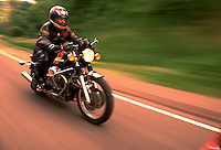 A motorcyle rider speeds down a blurred roadway. mototcycles, motorcyclist, transportation, speed.