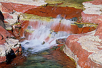 Water flows over the red and green argillite rock in Red Rock Canyon<br /> Waterton Lakes National Park<br /> Alberta<br /> Canada