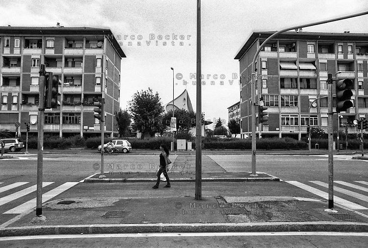 Milano, quartiere Quarto Oggiaro, periferia nord. Lungo la Via Amoretti: semafori, palazzi e chiesa --- Milan, Quarto Oggiaro district, north periphery. Along Amoretti street: street lamps, buildings, a church