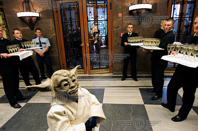 Waiters stand by with glasses of champagne as a guest, dressed as Yoda, a character from the science fiction film 'Star Wars', arrives for the film premiere at the Soviet-built Palace of Culture.