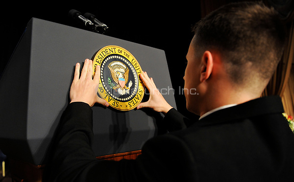 A White House aide puts the seal of the U.S President  on the podium before the White House Correspondents' Association Dinner at the Washington Hilton in Washington, DC, on Saturday, May 1, 2010.<br /> Credit: Olivier Douliery / Pool via CNP /MediaPunch